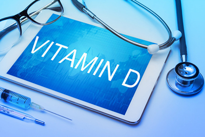Vitamin D word on tablet screen with medical equipment on backgr